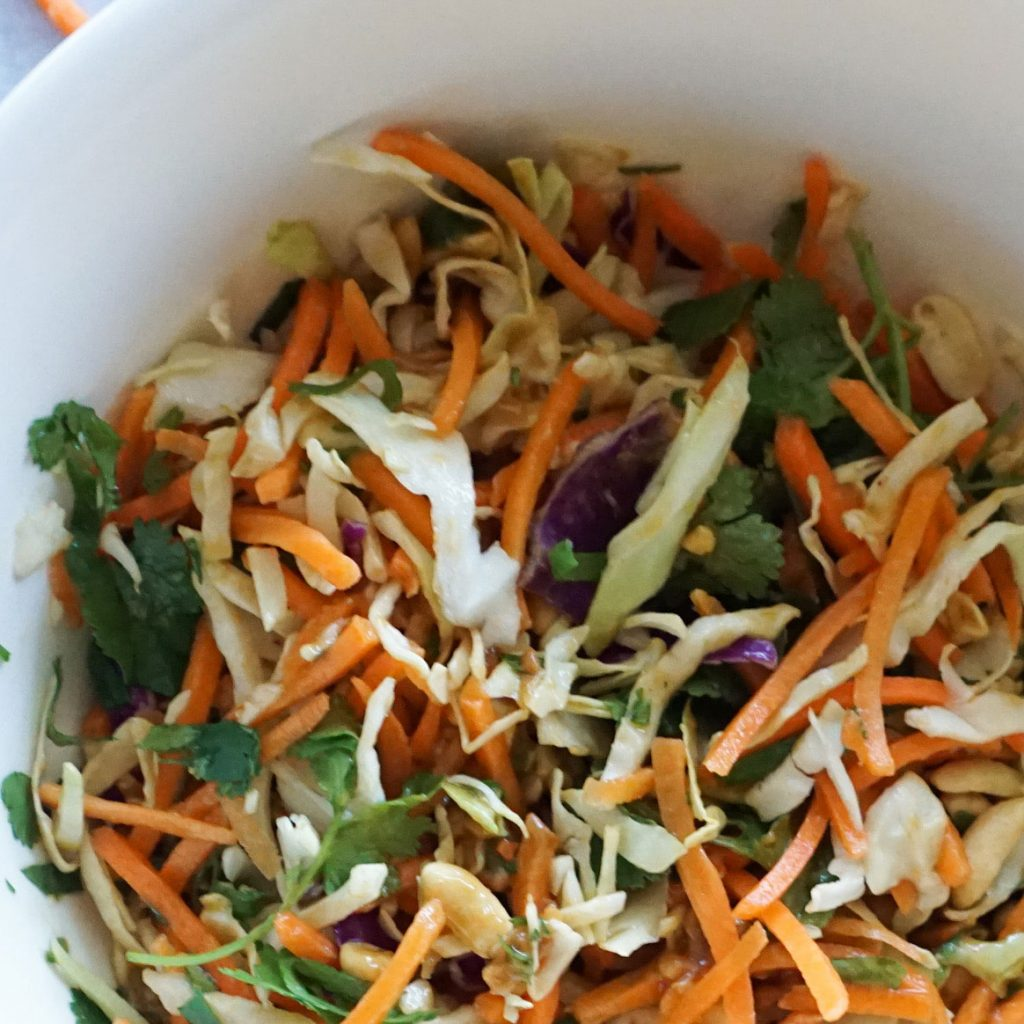 A white bowl is filled with shredded carrots, shredded coleslaw, chopped cilantro and peanuts. It is mixed together with a homemade peanut sauce on top.