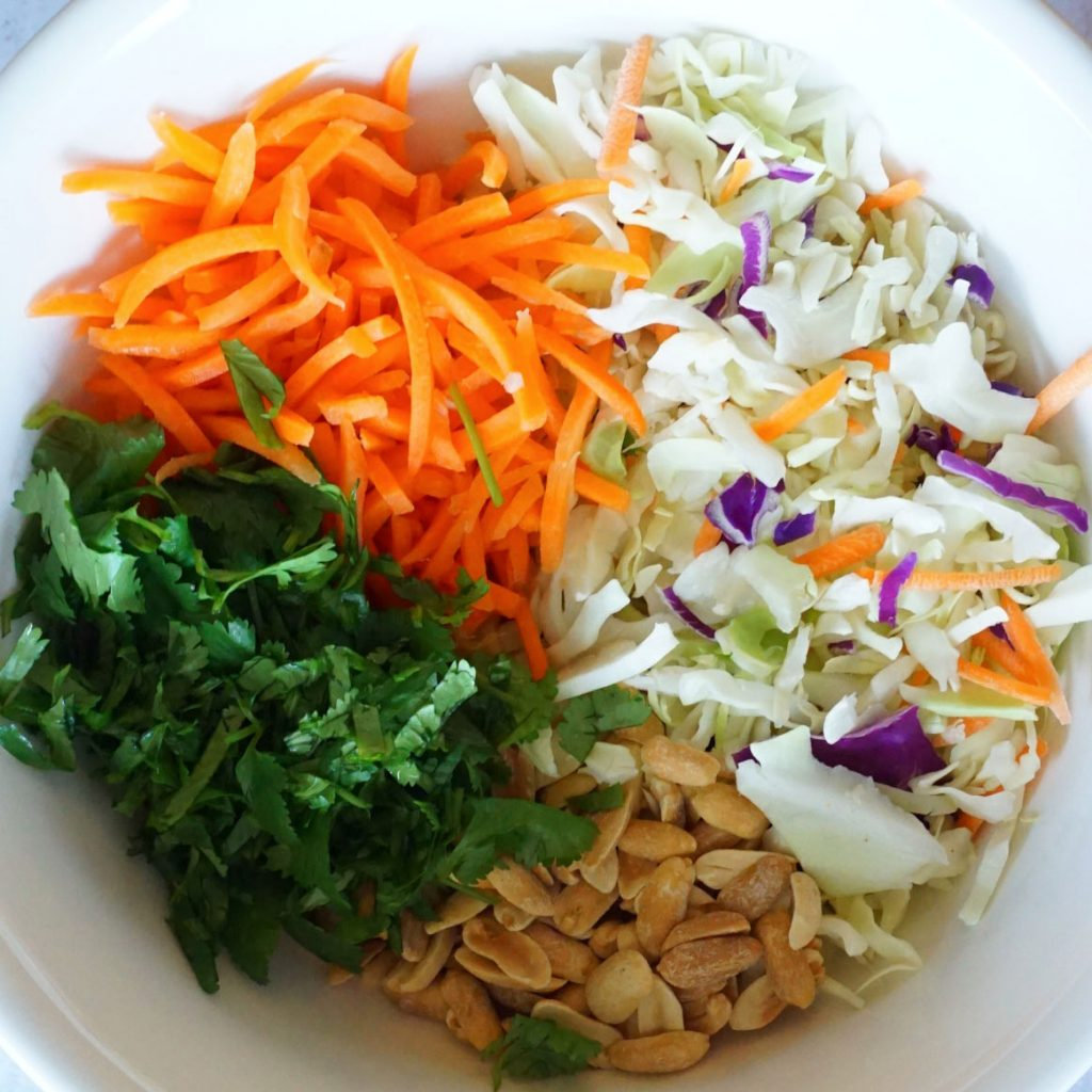 A white bowl is filled with shredded carrots, shredded coleslaw mix, chopped cilantro and peanuts. Each item is in an individual pile and they are all touching in the middle.