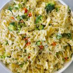 Bowtie pasta with cut tomatoes, cucumbers, carrots and broccoli are in a large white bowl.