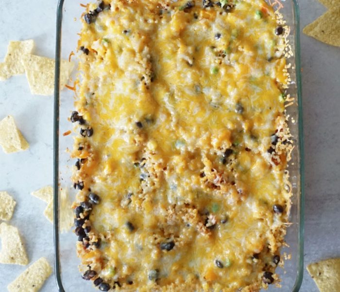 A rectangular glass baking dish is full of bubbly, cheesy Mexican quinoa casserole. There are tortilla chips sprinkled all around the dish.