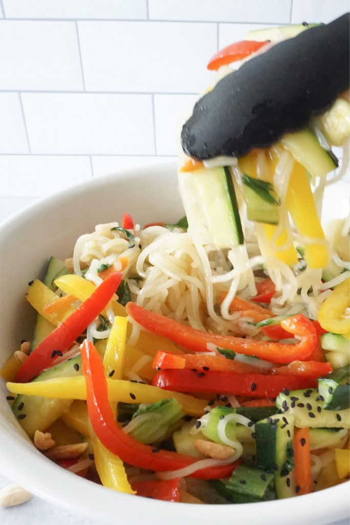 A small white bowl is filled with Pad Thai noodles, sliced cucumbers, carrots and bell peppers. The noodles are topped with crushed peanuts and sesame seeds. A pair of black cooking thongs is hovering over the bowl lifting a scope of pad thai out.