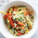 A small white bowl is filled with Pad Thai noodles, sliced cucumbers, carrots and bell peppers. The noodles are topped with crushed peanuts and sesame seeds.