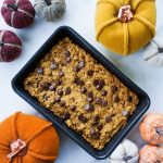 A rectangular baking dish sits on a white counter top with small felt pumpkins surrounding it. There are golden brown pumpkin oat bars in it.