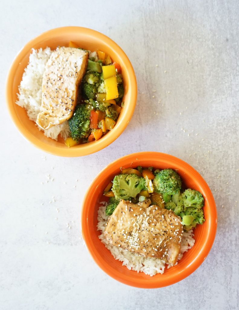 A yellow and an orange bowl are diagonal from each other. They are filled with  a piece of salmon, white rice, broccoli and bell peppers.