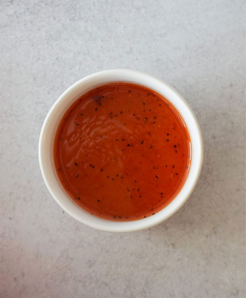 A small white bowl is full of bright orange spicy dressing.