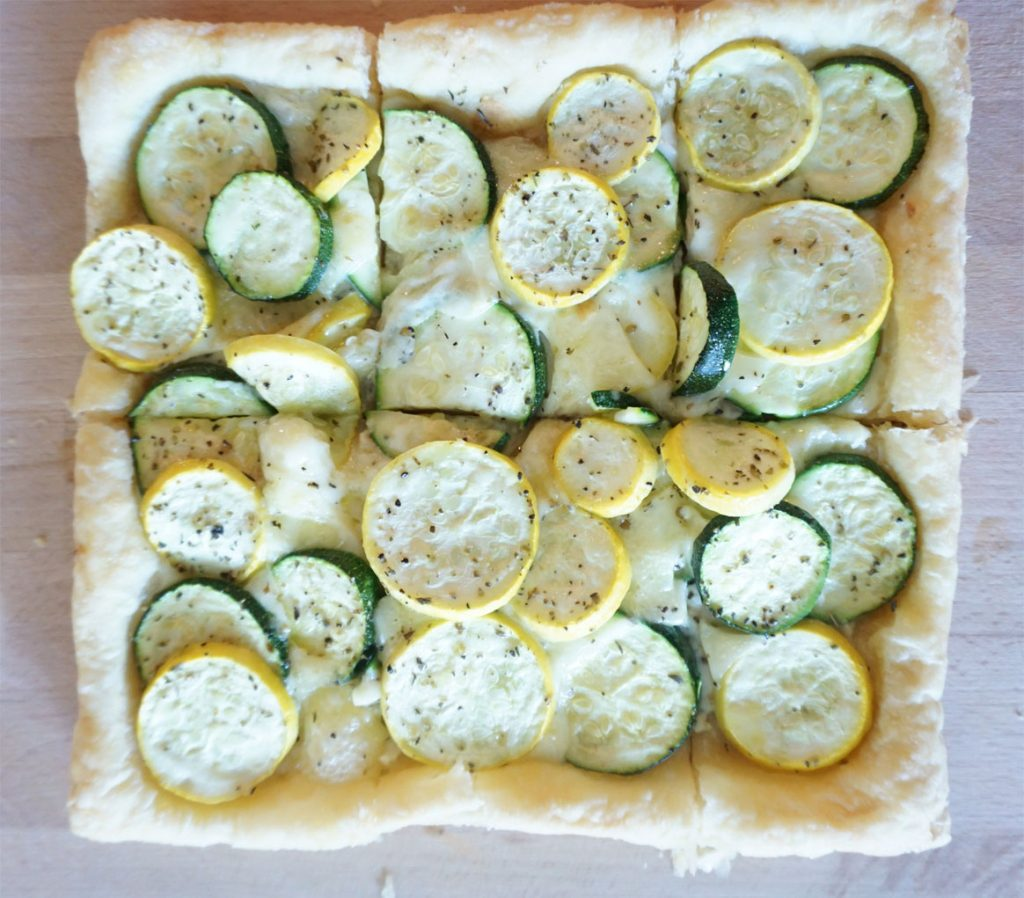 A square squash puff pastry tart sits on a rectangular wooden cutting board.