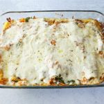 A rectangular glass baking dish is full of roasted vegetable lasagna with melted cheese on top.
